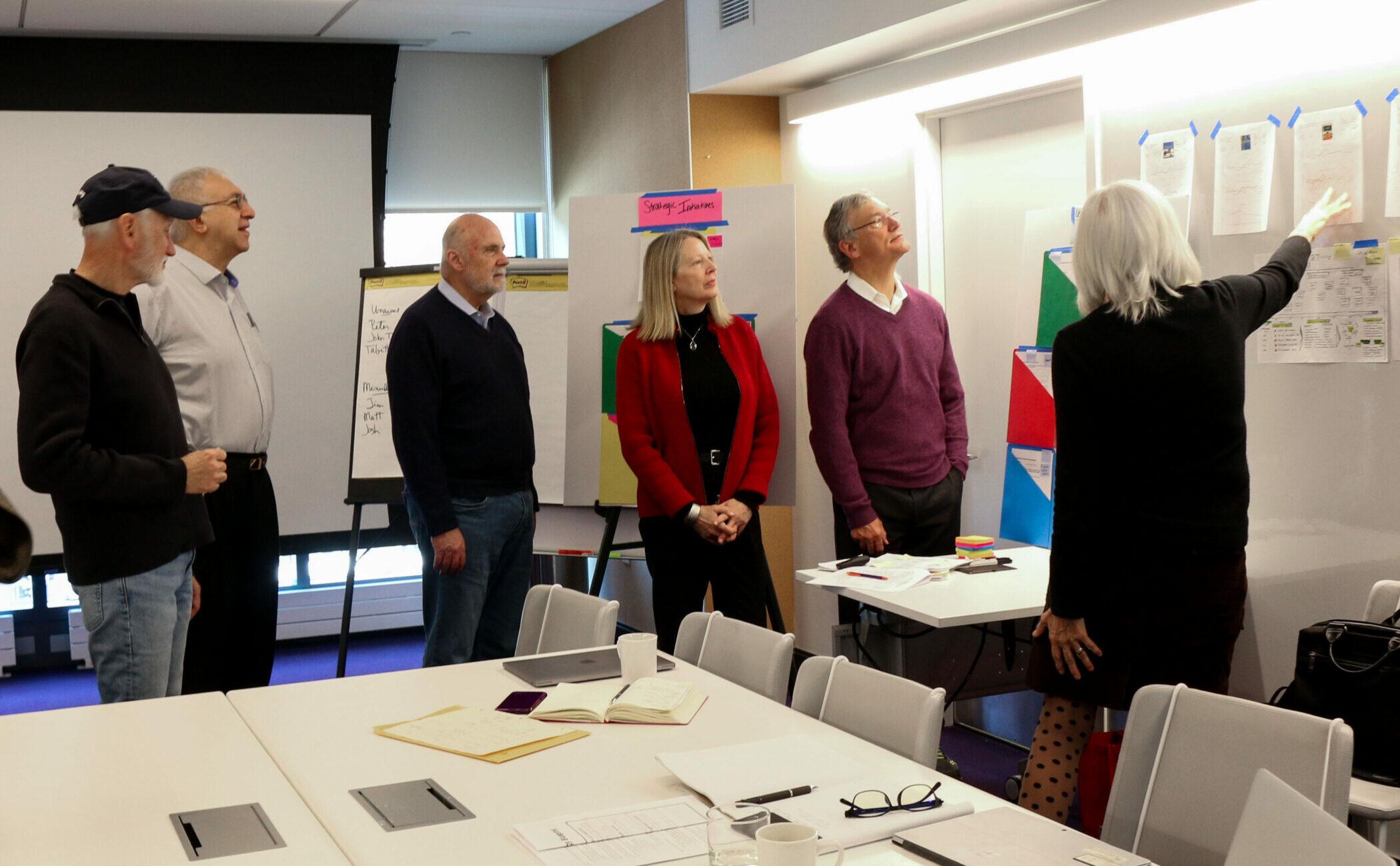 Jean talking to board of directors at a visual wall